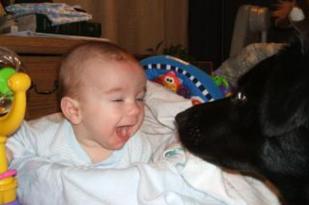 baby laughing to best friend dog