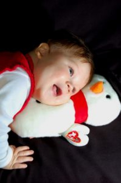 happy boy huging snowman lying on the bed