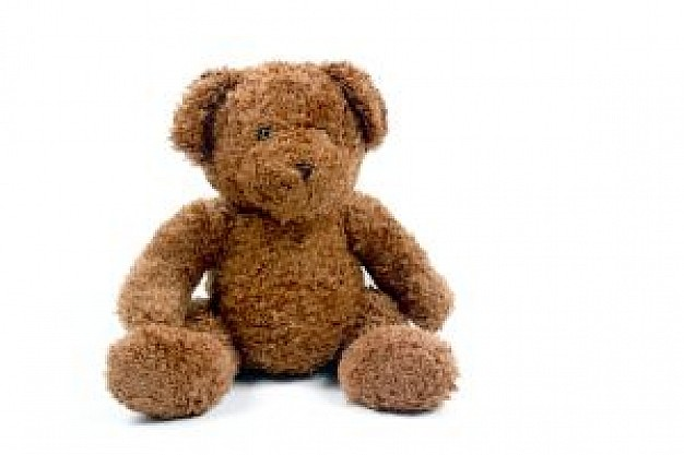 teddy bear sitting at white surface